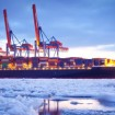 A container ship sits in the icy waters of a commercial port.