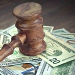 A judges gavel hits a pile of money