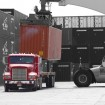 A container being placed on a truck at port.