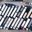 An aerial view of two rows of parked tractor trailers.