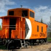 Orange Canada Pacific train car sitting on tracks.