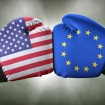 Two boxing gloves hit each other, one with the American flag and one with the EU flag.