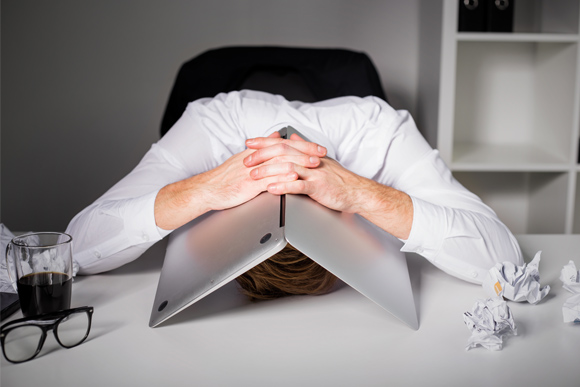 Man with head under laptop, frustrated