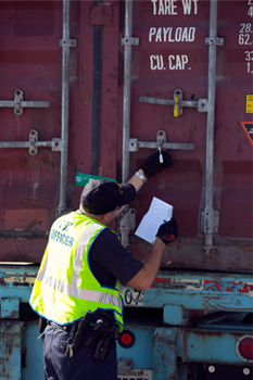 CBP officer inspects container with seal.
