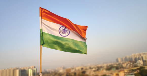 The India flag overlooking an Indian city.